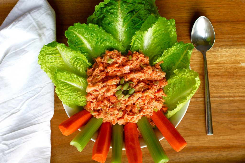 Salmon salad made with chickpea mayonnaise on a bed of romaine lettuce surrounded by carrots and celery