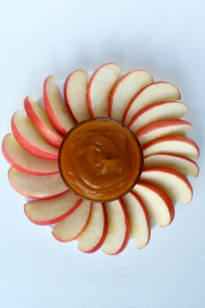 Vegan caramel in a bowl surrounded by sliced apples. runcooklaugh.com