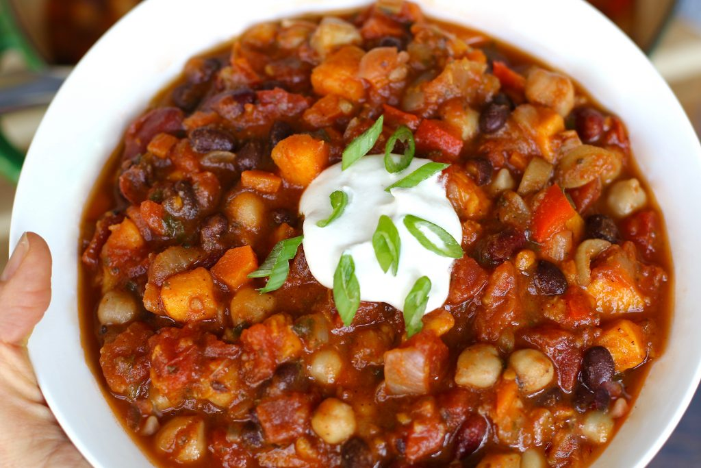 Vegan Chili in a bowl with cashew sour cream, scallions