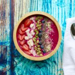 A smoothie bowl on a table garnished with strawberries, sliced almonds, blueberries, pumpkin seeds, hemp and chia seeds.